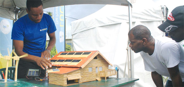 Image of a LUCELEC employee demonstrates to patrons how a solar photovoltaic system works.