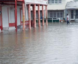A lone pedestrian walks through flooded city street last Saturday.