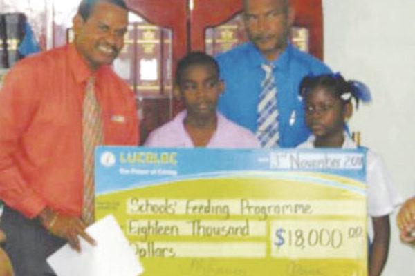 Image of Joseph presenting LUCELEC's $18,000 cheque.