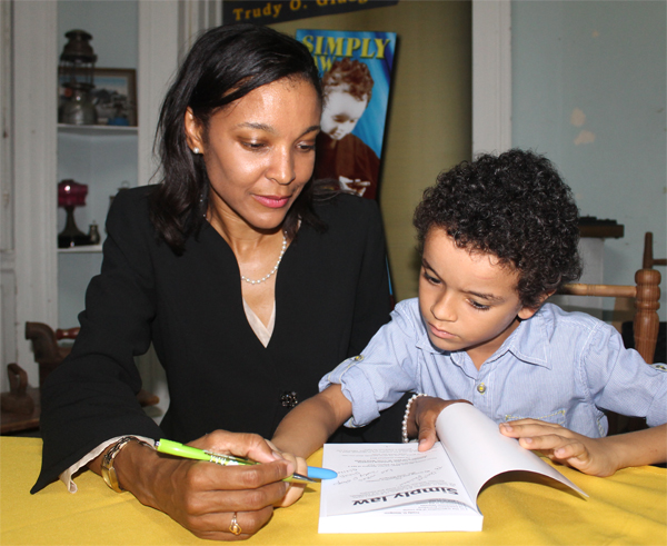 """Trudy Glasgow and son, Ethan, signing copies at last week Thursday's launch of """"Simply Law"""". [Photo: Stan Bishop]"""