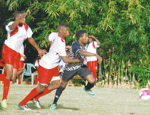 IMAGE: No letting up for the ball as players from both teams go in hot pursuit. [PHOTO: Anthony De Beauville]