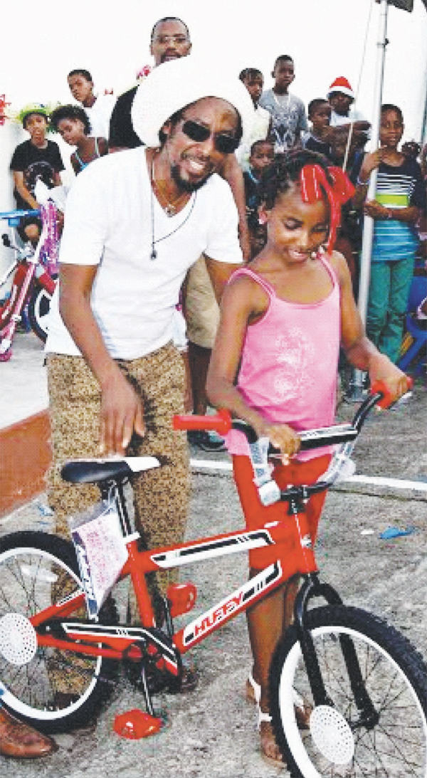 Weekes presenting a child with a new bicycle.