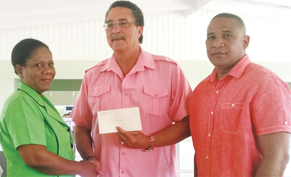Mrs Gustave receives the cheque from Prime Minister Anthony. High Commissioner Hilaire is at right.