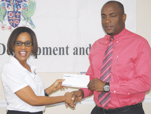 (L-R) General Manager Massy United Insurance Faye Miller presenting sponsorship cheque of EC $17, ooo.00 to St. Lucia Youth Development and Sports Minister Shawn Edward. [Photo: Anthony De Beauville]