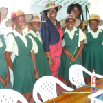 Members of Grow Well's Girls Circle model hats they are designing for the Governor General.