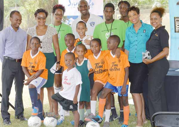 LIME's Sharlene Jn Baptiste, Sandals Partners and Trevor Daniel capture a moment with some of the future football stars and team members of the LIME/Trevor Daniel FDP at LIME Corinth, May 7.