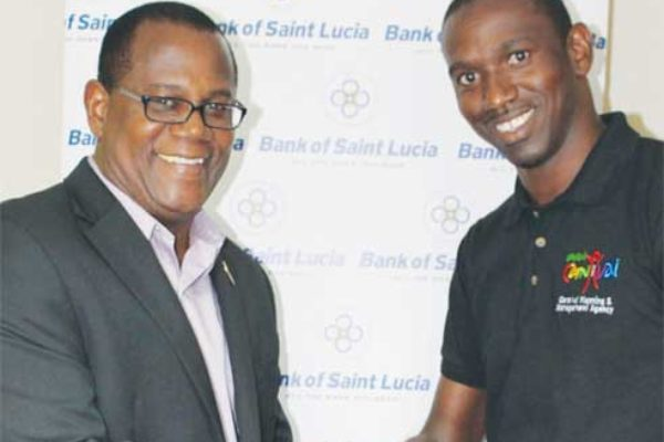 Image of BOSL General Manager HadynGittens which presents the Bank's sponsorship cheque to Devernant Joseph of the Carnival Planning and Management Agency (CPMA).