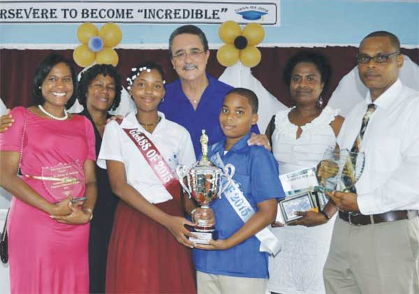 Image: Minister Anthony poses with the two winners (centrte) along with their parents/guardians.