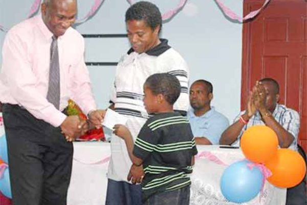 Education Minister Dr. Robert Lewis presents bursaries