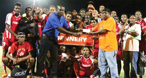 (L-R) Dennery team official Ali Henry receiving the winning cheque from Blackheart Director Brian Mc donald. [Photo DHP]