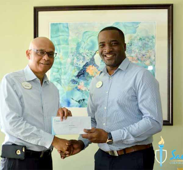 Trevor King (right) receives his scholarship grant from General Manager of Sandals Regency La Toc Golf Resort and Spa Michael James for his pursuit of a Master's Degree in Business Administration at the Australian Institute of Business.