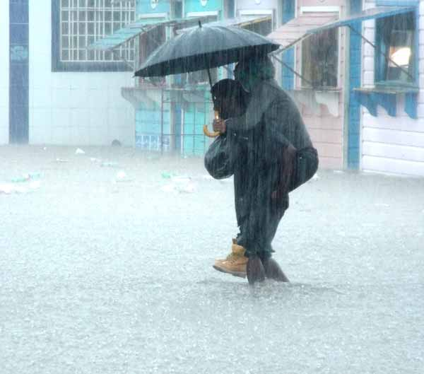 Image: A man carries a woman on his back across a flooded street.
