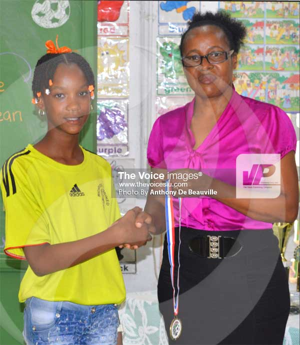 Image: Education Officer for District 5 Martineana Smith presenting a young and aspiring female footballer from Richfond Combined with her medal (PHOTO: Anthony De Beauville)