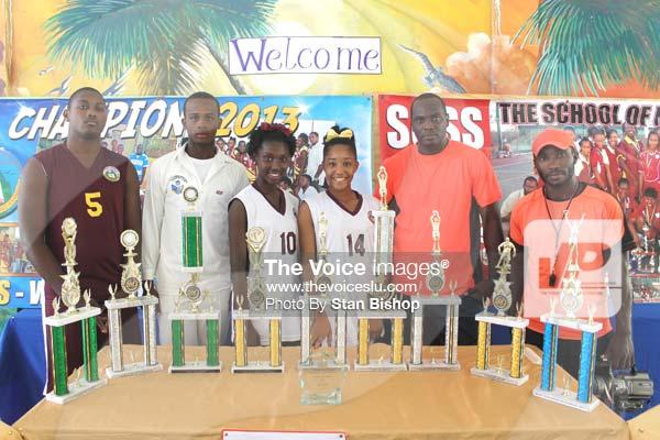 Image: Student athletes and their sports teachers flank their winning trophies. [PHOTO: Stan Bishop]
