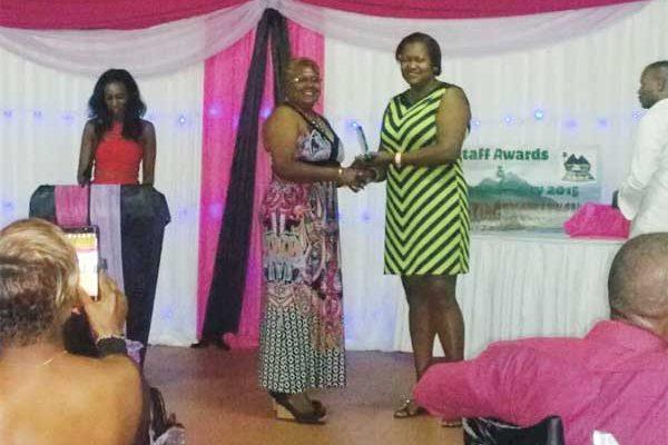 Sirmantha Denys gets a long service award from SRDF Director Gloria Junai.