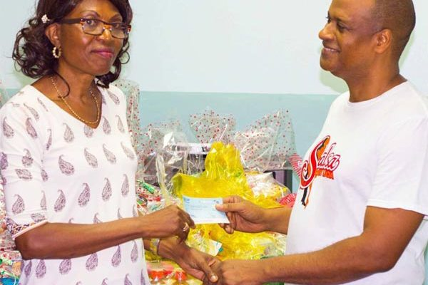 Image: Dr. St. Rose presents a hamper and cheque to Ms.Prisca St. Paul of Upton Gardens.