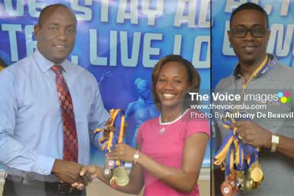 Image: Minister presenting medals to representatives from District 3 SolangePettie and Lorne Theophilus District 7. (PHOTOS BY: Anthony De Beauville)