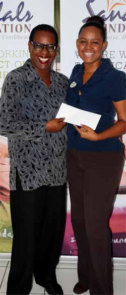 Ms.Laborde (left) receives Sandals cheque.
