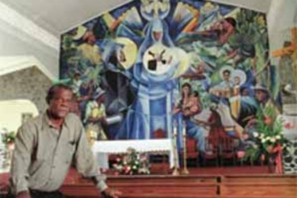 Sir Dunstan St. Omer with his mural at Jacmel Catholic Church.