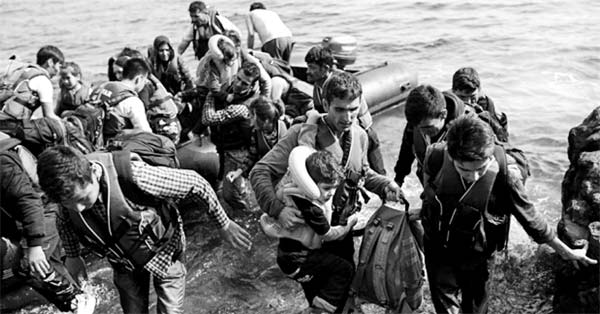 Syrian refugees disembarking an inflatable raft on the Greek island, Lesbos. [PHOTO: AngelosTzortzinis/Getty]