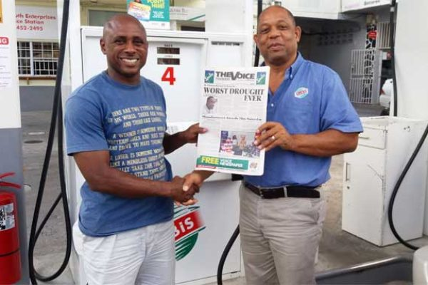 Image: Etienne (right) presents a copy of The VOICE to a customer.