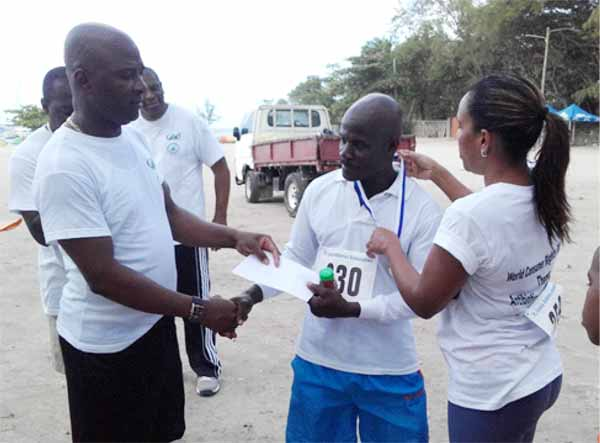 Image: This participant, who is seen here receiving his prize from the Permanent Secretary, registered the morning of the walk and was the first participant to get to Pigeon Island.