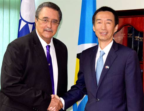 Ambassador Mou and Prime Minister Anthony shake hands at the cheque presentation ceremony