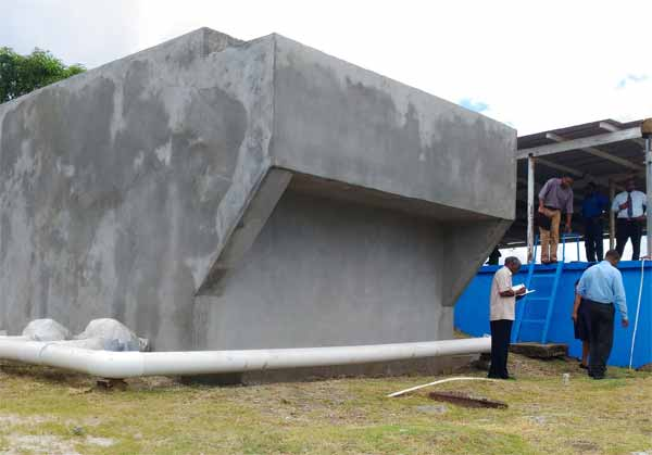 Image: The Roughing Filter (left) standing next to the main holding tank at the Micoud Water Treatment Plant.