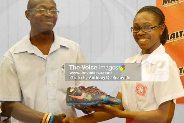 Image: Youth and Sports Officer Ligorious Marquis presenting a pair of track shoes to a CCSS student [PHOTOl Anthony De Beauville]