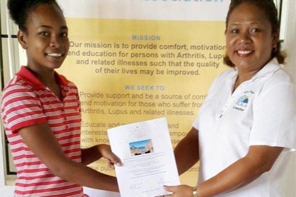 In picture, ZandraPerreira, Executive Member of SLALA presents the prize to raffle winner Celsianna Samuel.