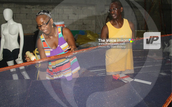img: Longtime Carnival supporter, John Joseph, (right) lends a helping hand at the mas camp. [PHOTO: Stan Bishop]