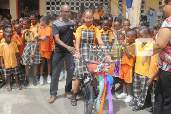 img: Universal Cycle Centre owner, Pius Raveneau, presents Arielle with her new BMX bicycle. [PHOTO: Stan Bishop]
