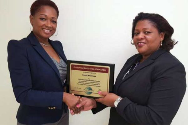 Image: Immediate Past President of the Public Service Toastmasters Club Michelle Charles (left) presents the Distinguished Award to Ms.Monrose