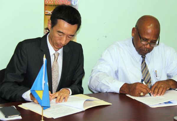 Image: Ambassador Mou and Minister Joseph sign the action plan.