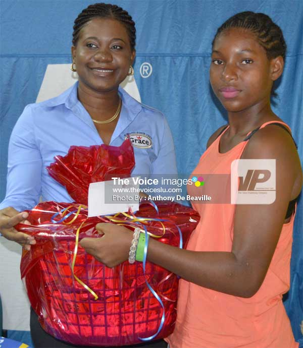 Image: (L-R) Grace Representative Keneene Betty Ford presenting Cassandra Wilfred with her grocery basket. (PHOTO: Anthony De Beaville)