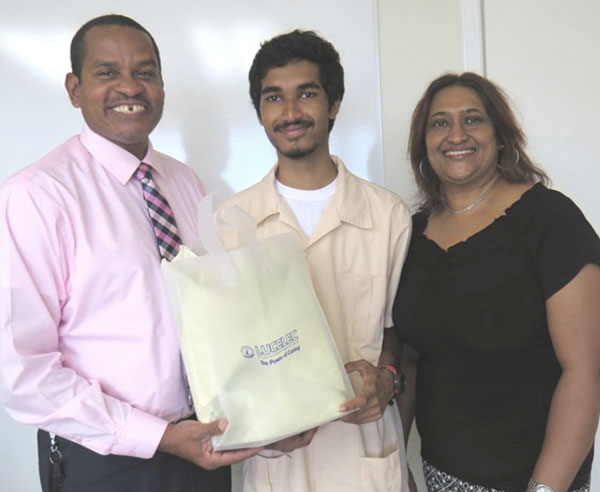 """img: """"LUCELEC SPISE 2016 Scholar Dion Recaii accompanied by his mother Sandra Recaii receiving a token from LUCELEC Corporate Communications Manager Roger Joseph"""""""