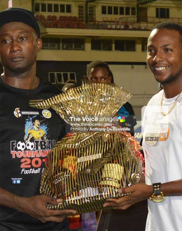 Image: Marchand striker Lincoln Phillip receiving his award from a St. Lucia Distillers representative for most goals scored in the tournament. (PHOTO: Anthony De Beauville)