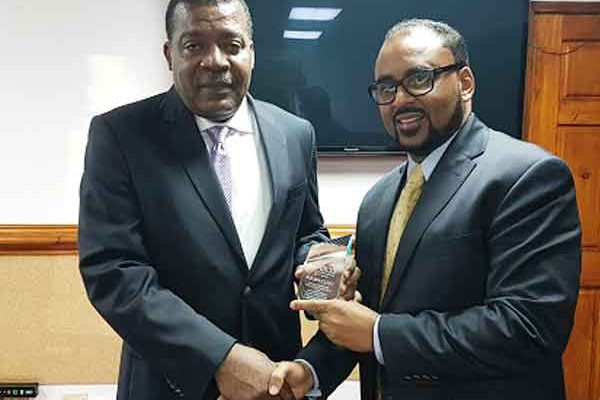 Image: CCRIF CEO, Mr. Isaac Anthony (right) presents a memento symbolizing payouts of US$23.4 million to Hon. Yves Bastien, Haiti's Minister of Finance at a ceremony on November 7, 2016. The payouts were due on Haiti's tropical cyclone and excess rainfall policies due to Hurricane Matthew and payment was paid 14 days after the event on October 17, 2016.