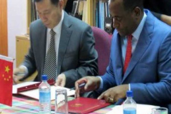 Image: Prime Minister Roosevelt Skerrit (right) and China Ambassador Lu Kun, signing agreements