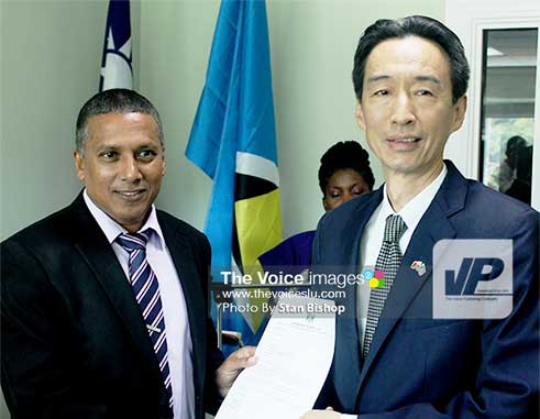 Image: Castries South-East MP, Guy Joseph, presents a letter of thanks to Ambassador Ray Mou. [PHOTO: Stan Bishop]