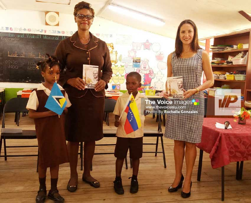 Image: Ambassador Escalona (right) makes the book presentation to school principal Margaret Gabriel and students. (PHOTO: Rochelle Gonzales)