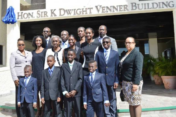 Image: The Venner family pose for a photo in front of the building.