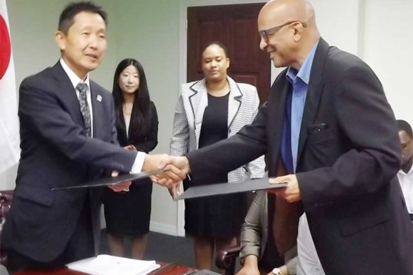 Image: The exchange of documents for the purchase of the ambulance between St. Jude Hospital Board Chairman, Dr. Ulric Mondesir and Japanese Ambassador Mr. Mitsuhiko Okada