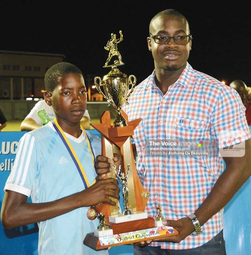 Image: (l-r) A representative from the Gros Islet team receiving the championship trophy from Sports Saint Lucia Online Managing Director Kenson Casimir;