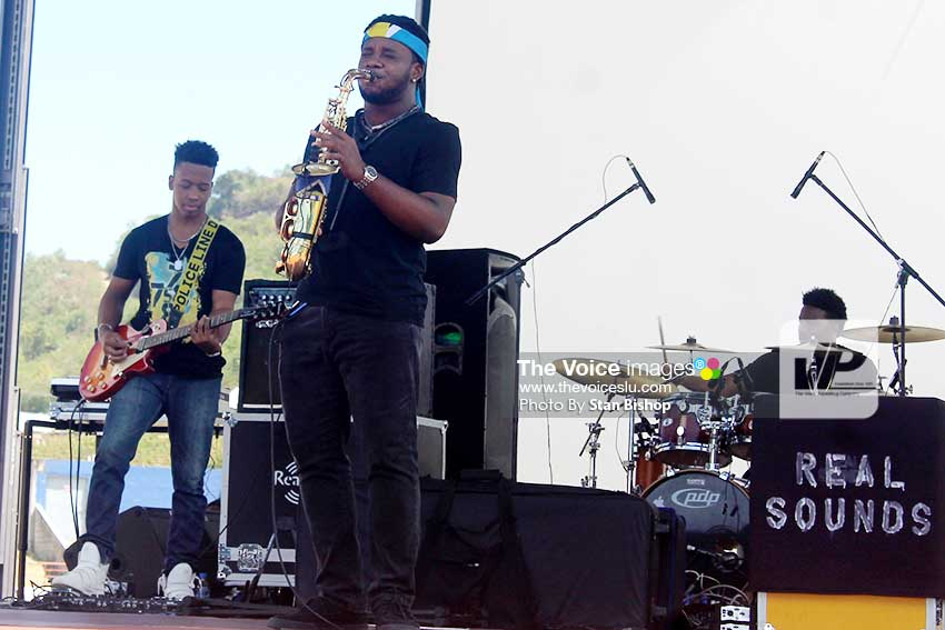 Image: Joseph playing the saxophone at this year's Independence Rally at Daren Sammy Cricket Ground. Guitarist Dwight Florent is at far left. [PHOTO: Stan Bishop]