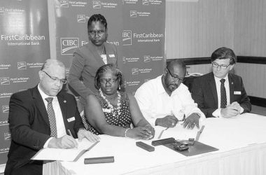 Image: Managing Director, Retail and International Business, CIBC FirstCaribbean, Mark St. Hill (left) signs the agreement while Chairman of the FirstPartnership Teresa Mortimer (second left) observes while Vice-Chairman David Massiah (third left) signs on
