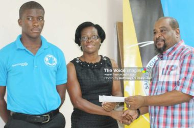 Image: Husbands presenting SLFA Scholarship to a parent of a young footballer. (PHOTO: Anthony De Beauville)