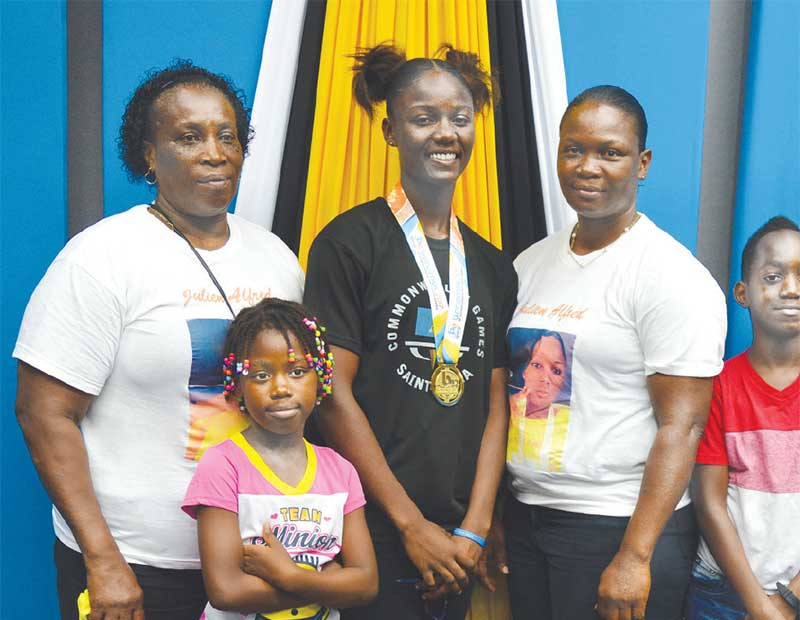 Image: (L-R) Sprint queen Julien Alfred proudly shows off her gold medal; Julien and her family members. (PHOTO: Anthony De Beauville)