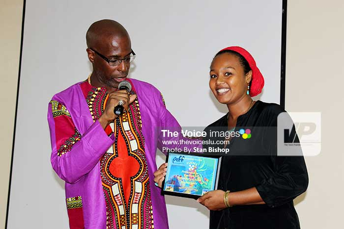 Image: Poet and activist, Xylaw, receives a plaque of recognition from Herman.