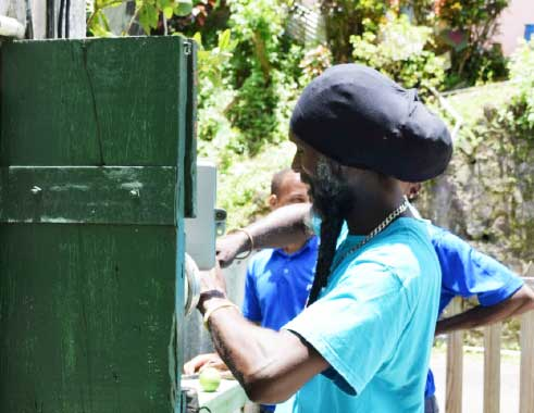 Image of Flow technicians at work in the community of Fond St. Jacques.